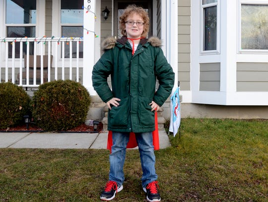 Ewan Drum, 8, poses with his cape in front of his home