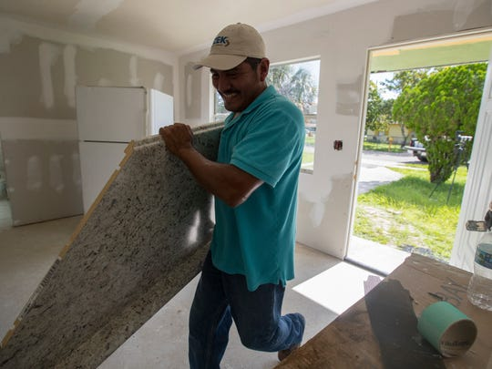 David Flores, an employee for Kings Classic, transports supplies while refurbishing this Dunbar home Tuesday, August 15, 2017.