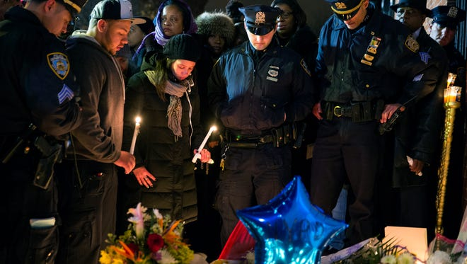 Police officers and other mourners stand in silence, Sunday, Dec. 21, 2014, during a candlelight vigil near the spot where two New York Police Department officers, sitting inside a patrol car the previous day, were shot by an armed man, killing them both. The assailant then went into a nearby subway station and committed suicide, police said.