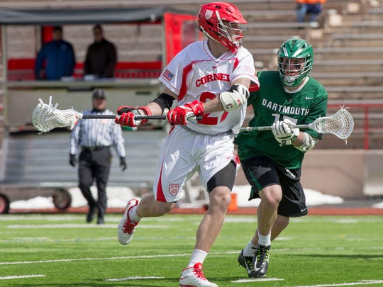 Cornell's John Edmonds looks to move the ball around Dartmouth's Taylor Topousis Saturday afternoon at Schoellkopf Field. Edmonds scored three goals in the Big Red's 8-2 victory, its fourth straight win and fifth straight over the Big Green.
