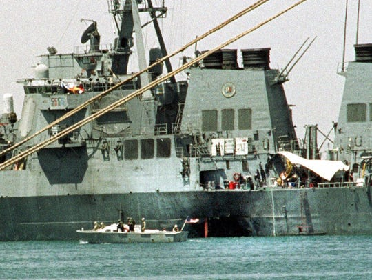A small boat guards the USS Cole in Aden, Yemen on
