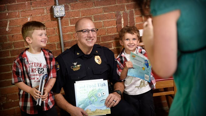 Lebanon city Chief of Police Todd Breiner read 'Pout Pout Fish goes to School' to children at the Lebanon Farmer's Market Saturday, Aug. 20, in the inaugural 'Police, Read to Me' program. Joey Morrisey, hopes the program will be a regular third Saturday of the month event. Children were given a free book to take home, and several posed with Breiner before leaving. Amdoh Good, 5, and his brother, Liam, 6, pose with the Chief of Police after listening to a story.