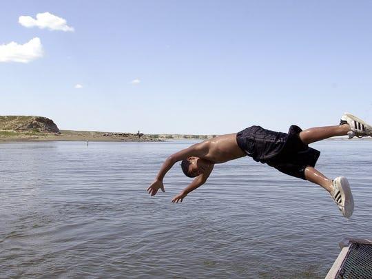 Steven Stike of Havre dives off a boat ramp at Fresno Reservoir.