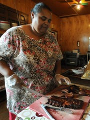 Bonnie Jackson cuts a slab of ribs at Leatha's Bar-B-Que Inn in Hattiesburg.