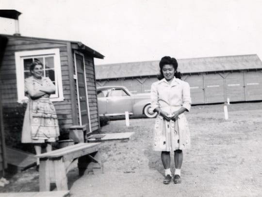 Georgette Yoshikai stands next to the fire chief's wife, Mrs. Rhodes, in the Caucasian area of Tulelake internment camp. The Caucasian camp workers enjoyed much nicer facilities.