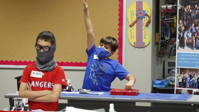 Amid concerns of the spread of COVID-19, Aiden Trabucco, right, wears a mask as he raises his hand to answer a question behind Anthony Gonzales during a summer STEM camp at Wylie High School Tuesday, July 14, 2020, in Wylie, Texas.