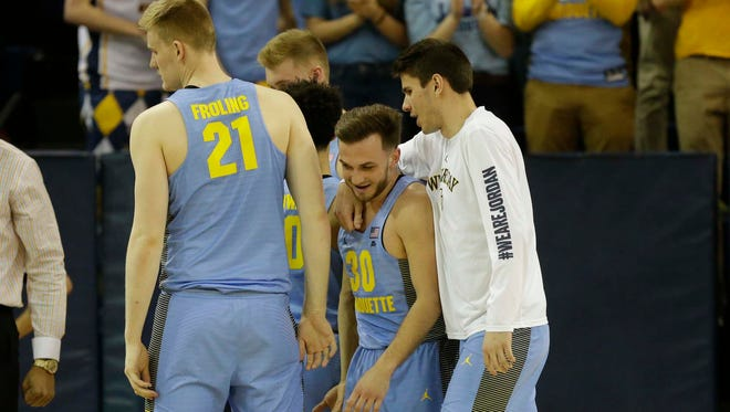 Marquette's Harry Froling, Andrew Rowsey and Mike Lelito celebrate during the victory over Oregon in the NIT second round on Sunday.