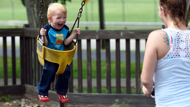 Anson Marksberry, 2, enjoys a boost from his aunt Chelsea as he swings along with his sister Harper (not pictured) at Kids Kingdom in Sunrise Park in Evansville Thursday.