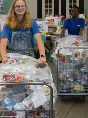 Student volunteers prepare snack bags to distribute to area school children in this file photo.