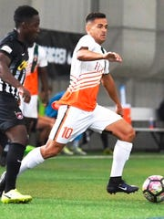 The Bucks' Daniel de Oliveira (10) carries the ball up field in Friday's PDL playoff match.