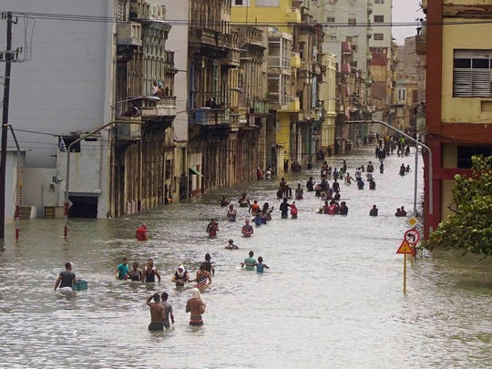 People move through flooded streets in Havana after