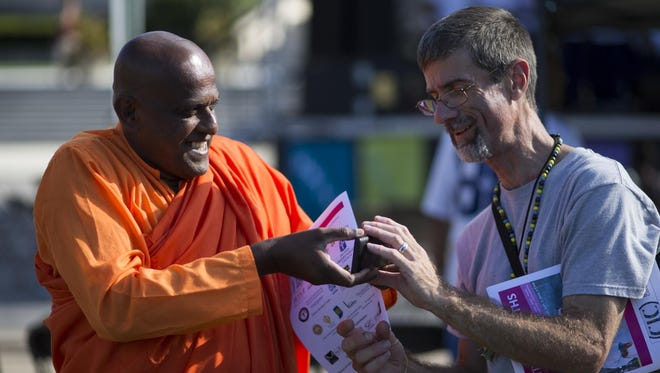 Rev. Matugama Mahanama Thero (left), of Hoagland, hands a camera to Bruce Allen, of Fort Wayne, at the Festival of Faiths in Downtown Indianapolis in 2014. This year's fesitval will be on Aug. 29-30.