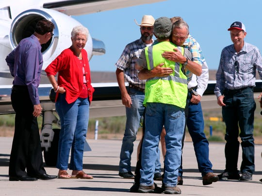 Rancher Dwight Hammond Jr., center, is embraced after arriving by private jet at the Burns Municipal Airport, Wednesday, July 11, 2018, in Burns, Ore.