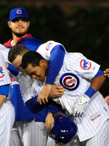 Cubs second baseman Addison Russell is mobbed by his