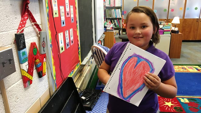 Second-grader Elyviana Cooley shows a heart she made on the first day of school at Hayes Elementary in Fremont.