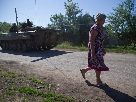 A woman passes Ukrainian servicemen as they ride on