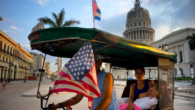 A taxi driver pedals his bicycle, decorated with Cuban and American flags, as he transports a woman holding a sleeping girl Tuesday, March 15, 2016, near the Capitolio in Havana. President Barack Obama will travel to Cuba on March 20.