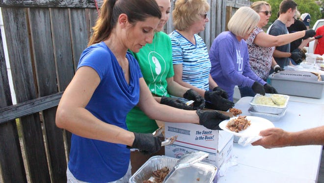 Michelle Leitao, left, Kimberlee Pagan and others from San Juan Del Rio Catholic Church in St. Johns County serve dinner on Friday at Dining with Dignity. The program provides free nightly meals at the corner of Bridge and Granada streets.