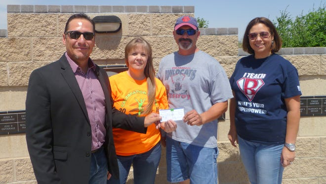 Board members, Ray Trejo (left)  and Benny Jasso, on behalf of  the Cancer Support Group of Deming and Luna County, Inc., accepted a check for $4,007 from Bataan Elementary School fifth grade teacher Kim Perea, second from left, and Principal Marlene Padron. The largest portion of the check came from the Celebration of Life Concert hosted by school. About $600 came from money that the staff paid to wear jeans on Wednesdays and the school's Kiwanis Club K-Kids donated $150 of profits they earned from their yard sale. The total includes a $365 donation made earlier in the year.