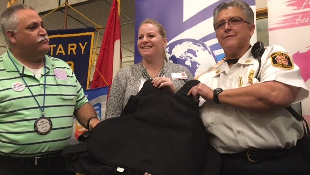 Past Garden City Rotary President Robert W. McLachlan and Garden City Hospital  spokeswoman Heather Walters give the protective vests to Fire Chief Cathy Harman.