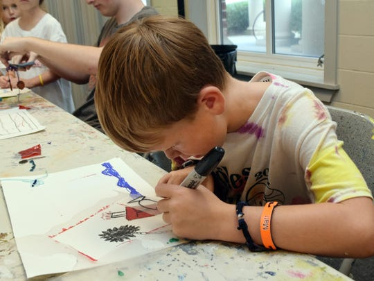Mathew Crenshaw works on the details of his mixed media collage in an art class he is taking at a summer art camp held at River Oaks Art Center Tuesday. The class is taught by Brenda Howell.