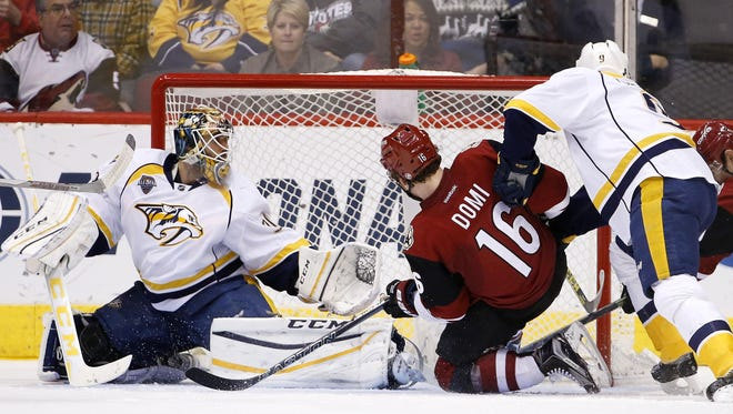 The Predators' Carter Hutton, left, makes a save on a shot by the Coyotes' Max Domi (16) as Filip Forsberg (9) defends in the third period Saturday.
