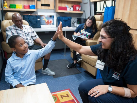 Occupational therapist Nicole Verrett high-fives Andrew Miller Jr., 6 of Camden, after Miller completed a basic developmental screening in Virtua's Pediatric Mobile Services Program unit in Camden on Wednesday, June 27, 2018.