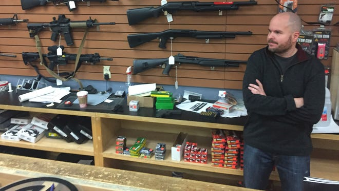 Firearms salesman Nathan Williams, 37, of Albuquerque, attends to customers at The Outdoorsman gun shop in Santa Fe, N.M., on Thursday, Jan. 5, 2017. Currents in the national debate over gun regulations are converging on New Mexico as the state Legislature prepares to meet. Under one proposal, federally licensed gun dealers would run background checks on sales between unlicensed sellers and buyers for a fee.