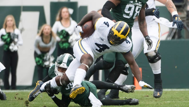 Michigan running back De'Veon Smith evades a tackle by Michigan State defensive back Justin Layne in the first quarter.