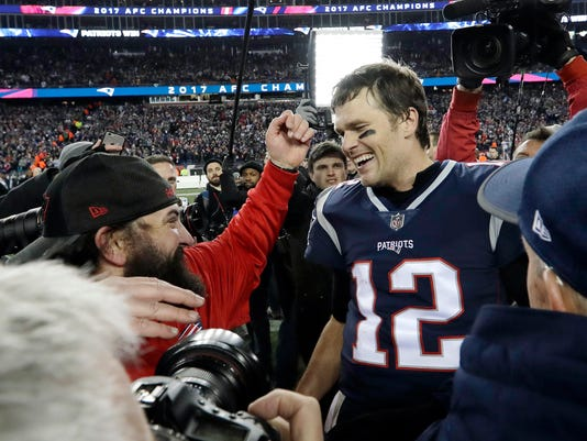 New England Patriots defensive coordinator Matt Patricia, left, reachess to embrace New England Patriots quarterback Tom Brady after the AFC championship NFL football game against the Jacksonville Jaguars, Sunday, Jan. 21, 2018, in Foxborough, Mass. (AP Photo/David J. Phillip)
