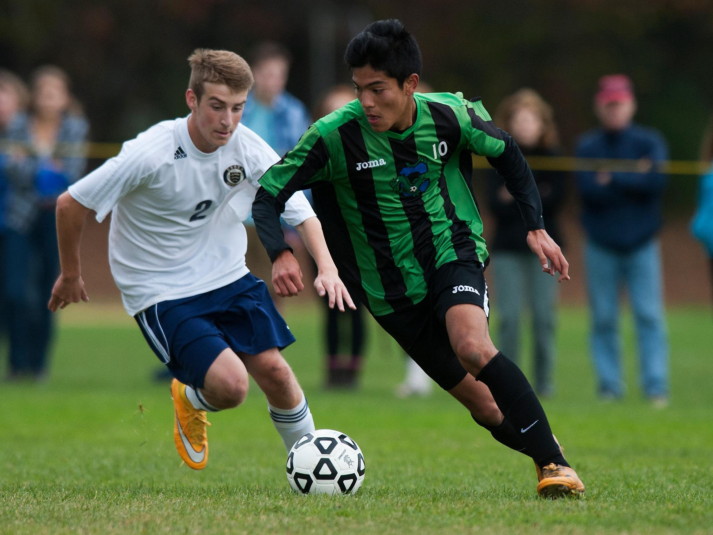 Colchester's Chris Zamarripa (10) runs past Essex's Aidan Whitney (2) with the ball during the boys playoff soccer game between the Colchester Lakers and the Essex Hornets at Essex High School on Saturday afternoon October 25, 2014 in Essex, Vermont (BRIAN JENKINS, for the Free Press)