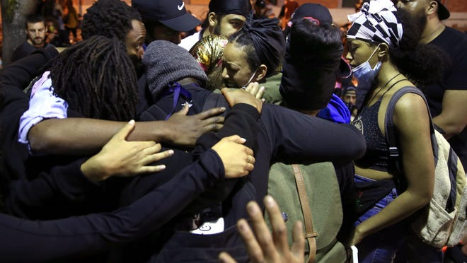 Black protesters embrace at the end of a protest march through the streets of Eugene on Wednesday. [Chris Pietsch/The Register-Guard] - registerguard.com