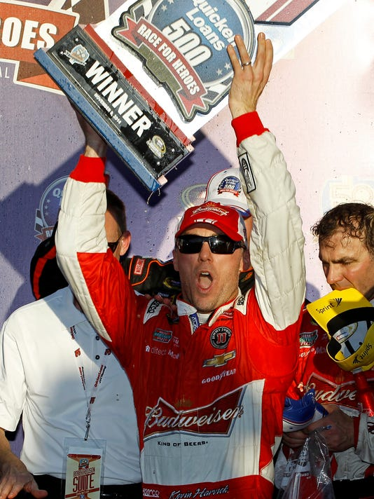 Driver Kevin Harvick celebrates with the trophy in victory lane after winning the Quicken Loans Race for Heroes 500 NASCAR Sprint Cup Series auto race at Phoenix International Raceway, Sunday, Nov. 9, 2014, in Avondale, Ariz. (AP Photo/Ralph Freso)