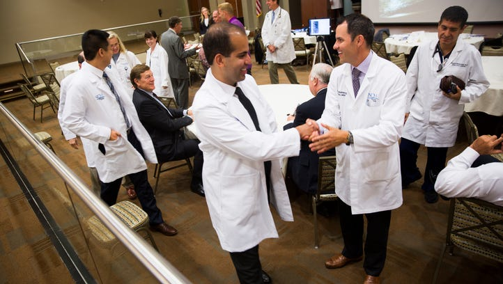 Residents shake hands with their mentors after the