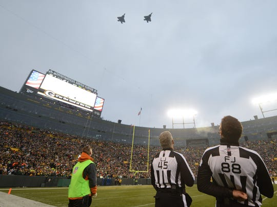 Referees watch as jets fly over during the national anthem at Lambeau Field before the Green Bay Packers game against the Philadelphia Eagles.