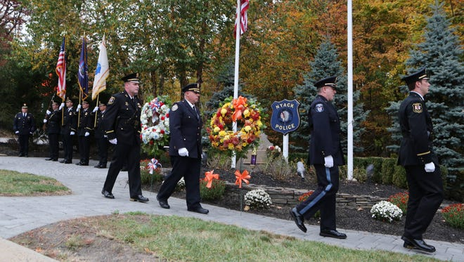 "Police officers walk past the memorial after placing the wreaths, during the 35th annual Brinks Memorial Service at the entrance to the Thruway on Mountainview Avenue in Nyack, Oct. 20, 2106. Nyack police Sgt. Edward O'Grady, Officer Waverly ""Chipper"" Brown and Brinks Guard Peter Paige were killed during a brazen robbery that began at the Nanuet Mall."