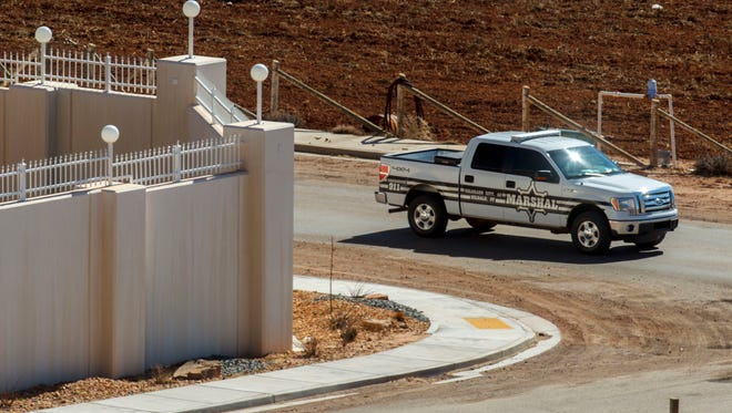 In this Feb. 18, 2013, file photo, a Marshal with the Hildale/Colorado City Town Marshals patrols along the walls of a residential compound built for polygamous church leader Warren Jeffs in Hildale.