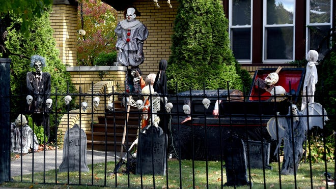 A skeleton rises from a coffin at an area home, along with zombies, a clown and skulls lined on a black fence. Local and state officials announced health and safety guidelines for celebrating Halloween during the pandemic.