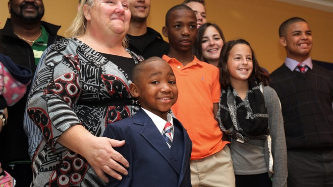 Janet Hans keeps her 4-year-old son, Naeim, close by as they take photographs with their extended family during a reception at the Ocean County Library in Toms River, Friday, after his adoption was finalized at the courthouse.