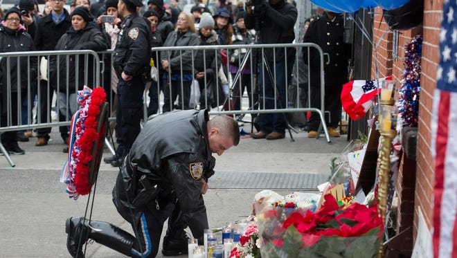 A police officer kneels at a makeshift memorial near the site where NYPD officers Rafael Ramos and Wenjian Liu were killed in Brooklyn on Monday. Police say Ismaaiyl Brinsley ambushed the two officers in their patrol car, fatally shooting them before killing himself inside a subway station.