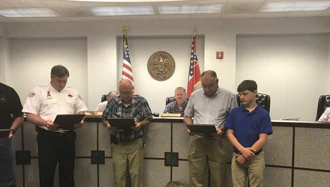 Lamar County Supervisor Dale Lucus reads a resolution honoring fallen Sumrall firefighter Loretta Ann Sykes to her grandson Chris Carver, 13.