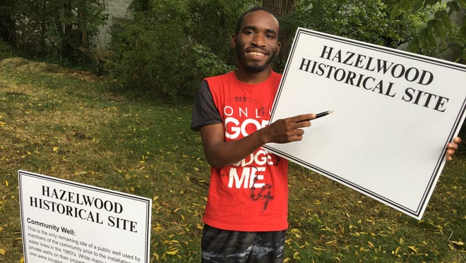 Joshua White works on signs that will highlight points of interest along the Hazelwood walkathon route.