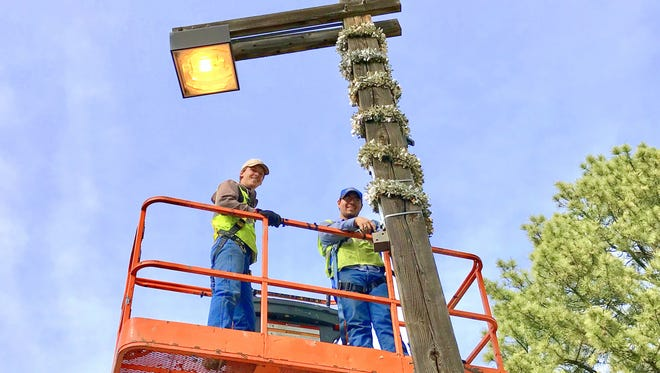 Jeremy Nocella, left, and Tristan Baca of the village Parks and Recreation Department wrap one of the light poles in midtown Ruidoso.