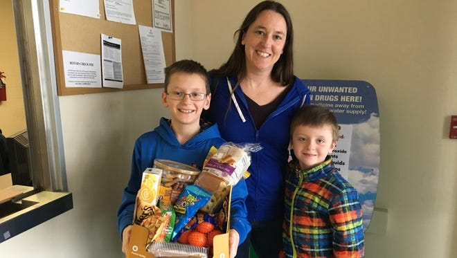 Erin Strutt, center, with her boys, Owen, 10, and Colin, 6, dropped a box of treats at Springettsbury Township Police Department and Northern York County Regional Police Department Friday afternoon. Strutt said it was their way of saying thanks to the police officers who have been busy this week investigating threats made against Central York School District.