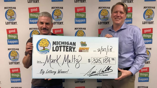 Mark Maltz collects a check for his Fast Cash Jackpot Slots prize from Michigan Lottery Commissioner, Aric Nesbitt.