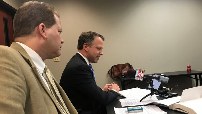 Attorney Jamie Hollin speaks at Friday's election commission meeting as attorney Jim Roberts, left, looks on.