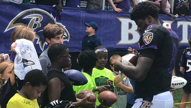 Former Louisville quarterback Lamar Jackson signs a football for a young fan after practice at Baltimore Ravens training camp on July 22, 2018, in Owings Mills, Md.