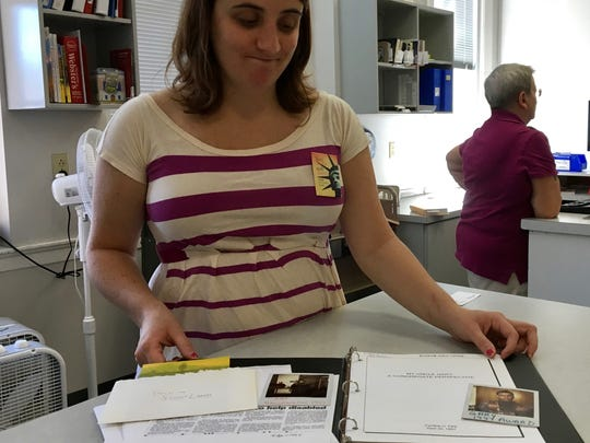 Kayla Payne, technology services librarian at Staunton Public Library stands behind the counter with a collection of stories and photographs of Gary Kiracofe kept in the family history and genealogy section of the library.
