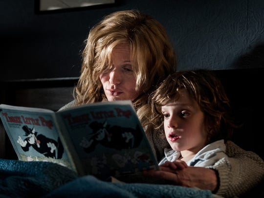 "Essie Davis stars as a single mom who reads a book to her son (Noah Wiseman) and unknowingly unleashes a monster in ""The Babadook."""