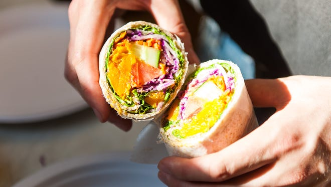 Wildflower Cafe owner Eric Nyman cracks open a veggie wrap. The eatery is the first stop on A Taste of Millville.
